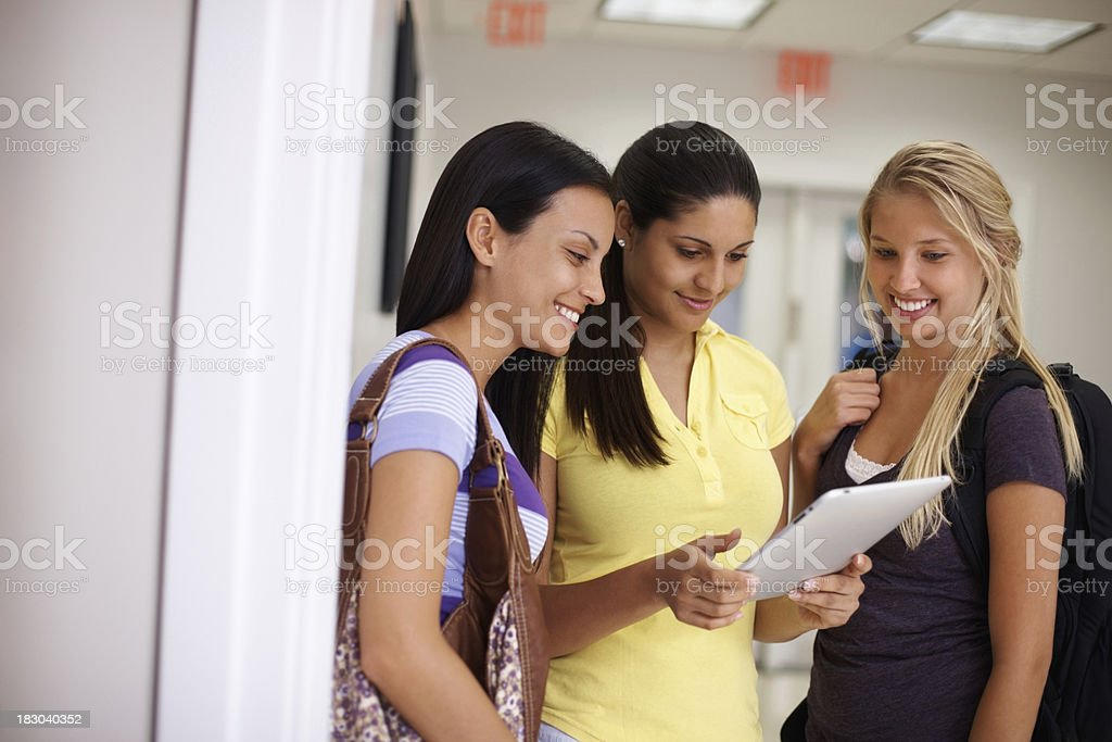 College girl standing with her friends while holding tabletpc royalty-free stock photo