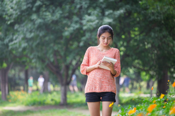 college girl students reading a book and walking - beautiful college girl pics stock photos and pictures
