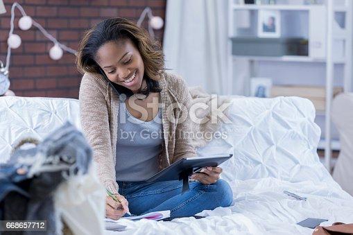 668442836 istock photo College girl talks on phone in dorm room 668657712