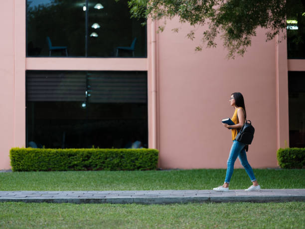College girl walking through campus stock photo