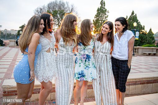 Six close girlfriends pose  for a group graduation photo on their college campus.