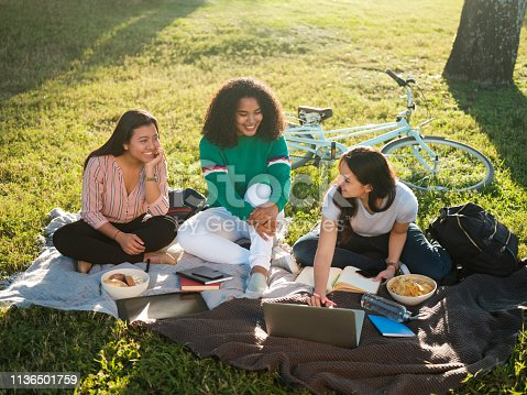 Three college girls studying together outside sitting on the ground with books and snacks.