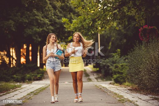 Front view of two smiling young women walking in campus, carrying books and backpacks.