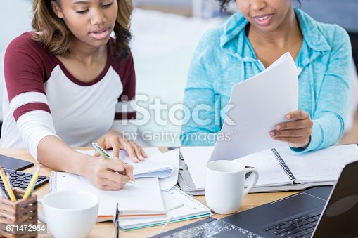 istock College girls work on a paper together 671472984
