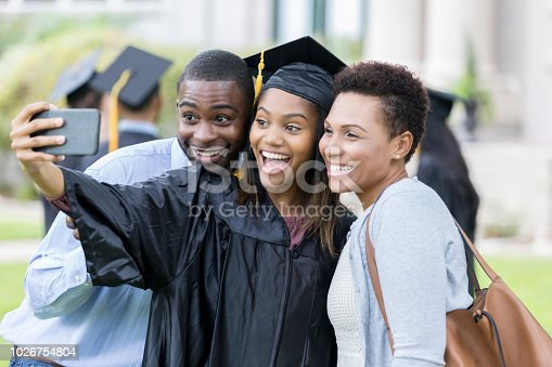 Excited African American college girl takes selfie with parents after graduating from college.