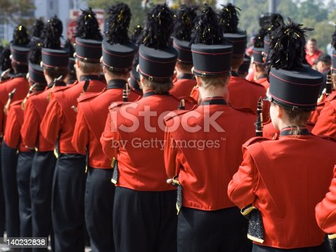 US College marching band in formation with red uniforms and black pants and hats, prior to football game.