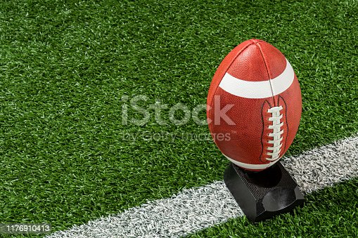 A college or high school leather American Football with a white stripe on each end, sitting on a black kicking tee that is on a white yard line of the turf field. The college and high school footballs have a white stripe on each end of the ball on only half the ball.
