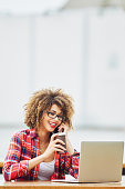 Young woman working on laptop and talking on mobile phone