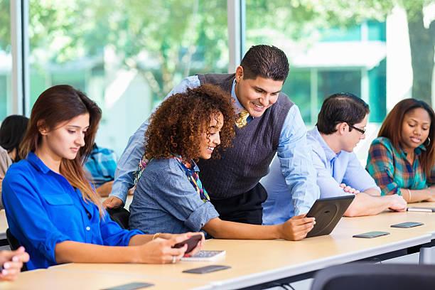 professor assistere studente universitario con digital tablet in classe - professore di scuola superiore foto e immagini stock