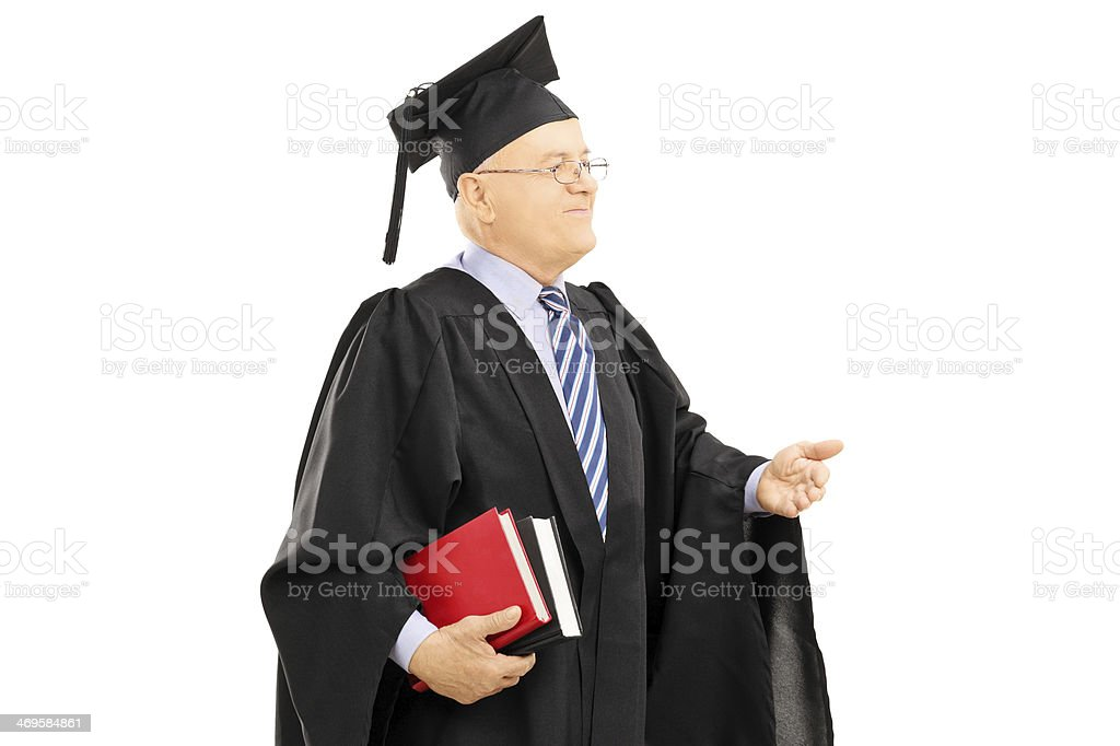 College professor in graduation gown holding book stock photo