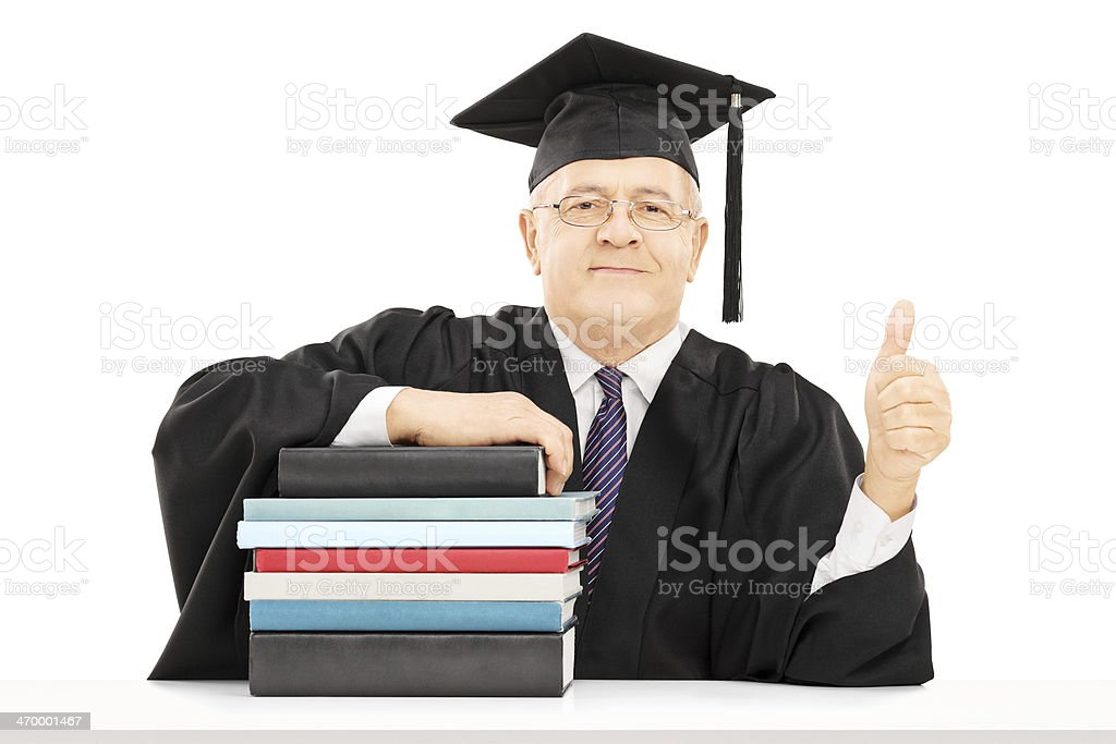College professor seated on table with books gesturing happiness stock photo