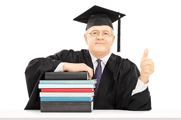 College professor seated on table with books gesturing happiness Middle aged college professor seated on table with stack of books and giving thumb up isolated on white background college dean stock pictures, royalty-free photos & images