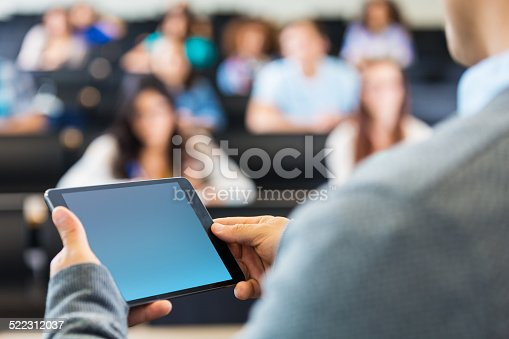 istock College professor using digital tablet while speaking in lecture hall 522312037