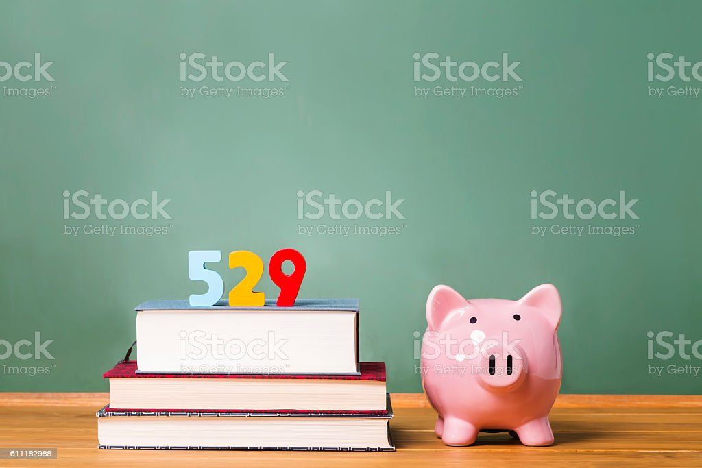 529 college savings plan theme with textbooks and piggy bank stock photo