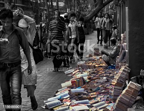 A bookseller sitting in his street side bookstore, pedestrian walking beside him. Most of the books are on footpath, as there is no permanent stall. This particular shop sells old books. This area is near Calcutta University campus at College Street. Kolkata, popularly known as 'Boipara', famous for large number of book stalls selling every kind of books and nearby different educational institutes. This is a heritage area, of historical socio-political importance. Office of large number of publication house are scattered throughout the area. Photo taken on 12/02/2017. Portion of the image has been made monochrome to make it more dramatic.
