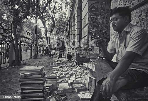 A bookseller sitting in his street side bookstore, busy looking at his phone. This particular shop sells old books. This area is near Calcutta University campus at College Street. Kolkata, popularly known as 'Boipara', famous for large number of book stalls selling every kind of books and nearby different educational institutes. This is a heritage area, of historical socio-political importance. Office of large number of publication house are scattered throughout the area. Photo taken on 12/02/2017