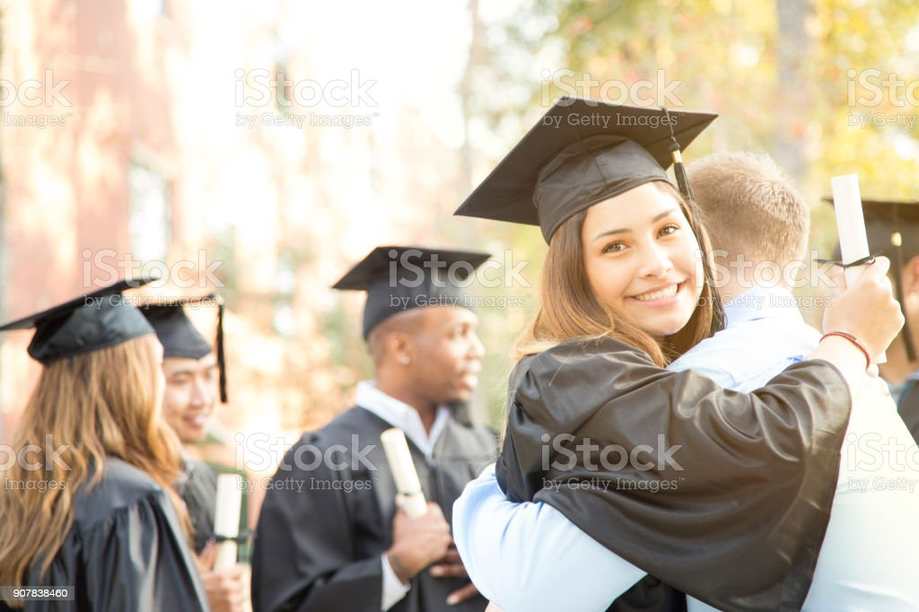 College student excitedly hugs father after graduation ceremony. royalty-free stock photo