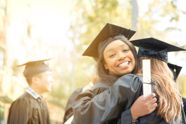 College student friends excitedly hug after graduation ceremony. stock photo
