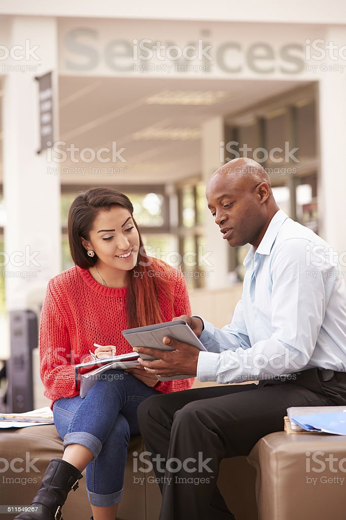 College Student Having Meeting With Tutor To Discuss Work stock photo
