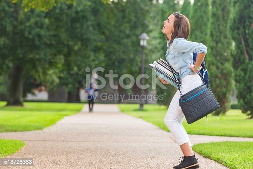 istock College student holding heavy books while walking on campus 518728383