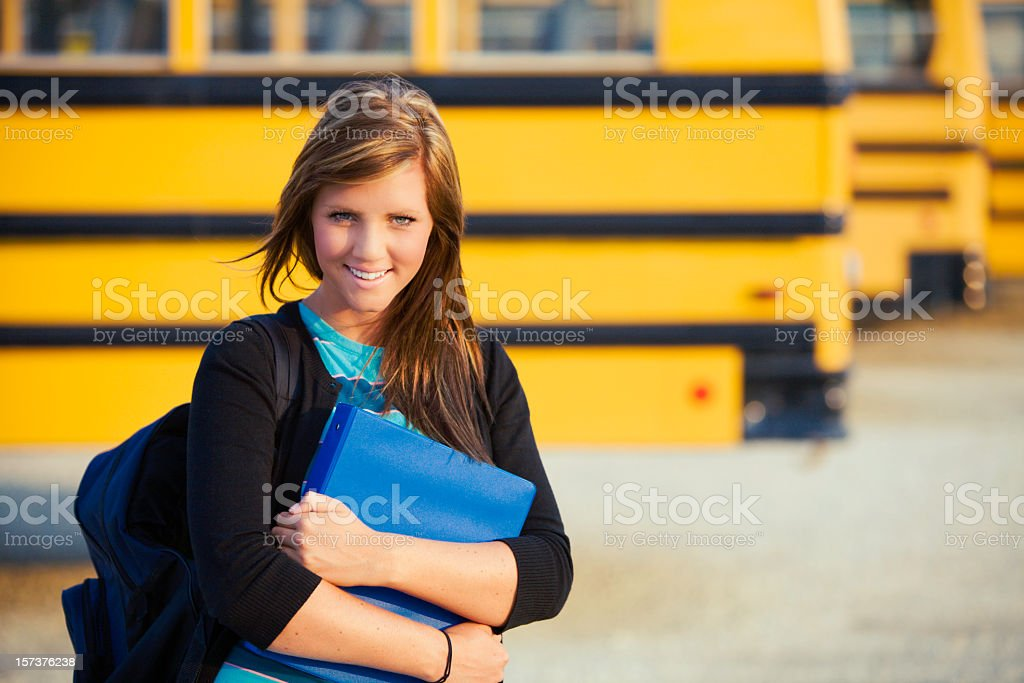 College student in front of rows of yellow school busses royalty-free stock photo