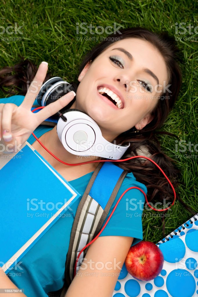 College student laying on grass with peace sign royalty-free stock photo
