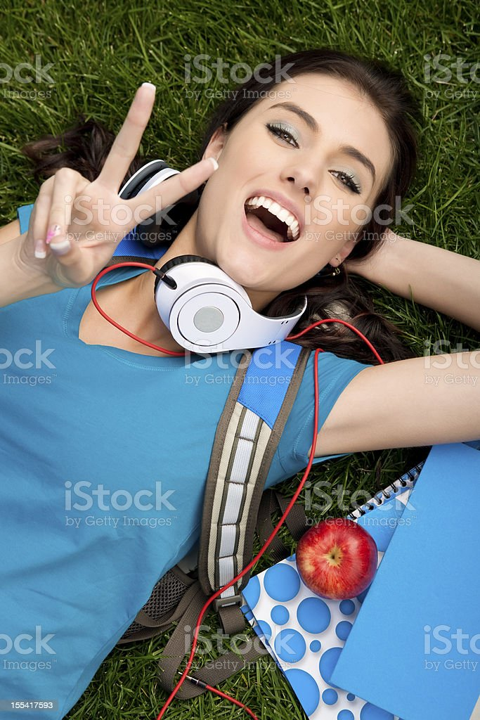 College student laying on grass with peace sign stock photo