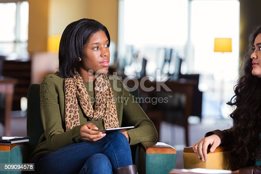1190039622istockphoto College student mentoring younger girl, meeting in library 509094578