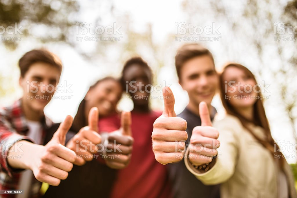 college student multiracial thumbs up at dusk stock photo