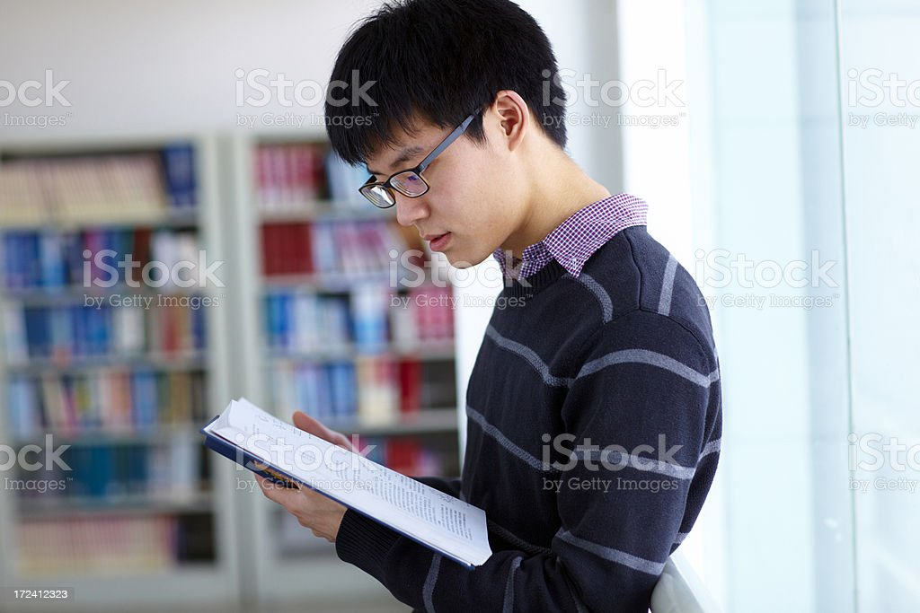 college student reading book in the library royalty-free stock photo