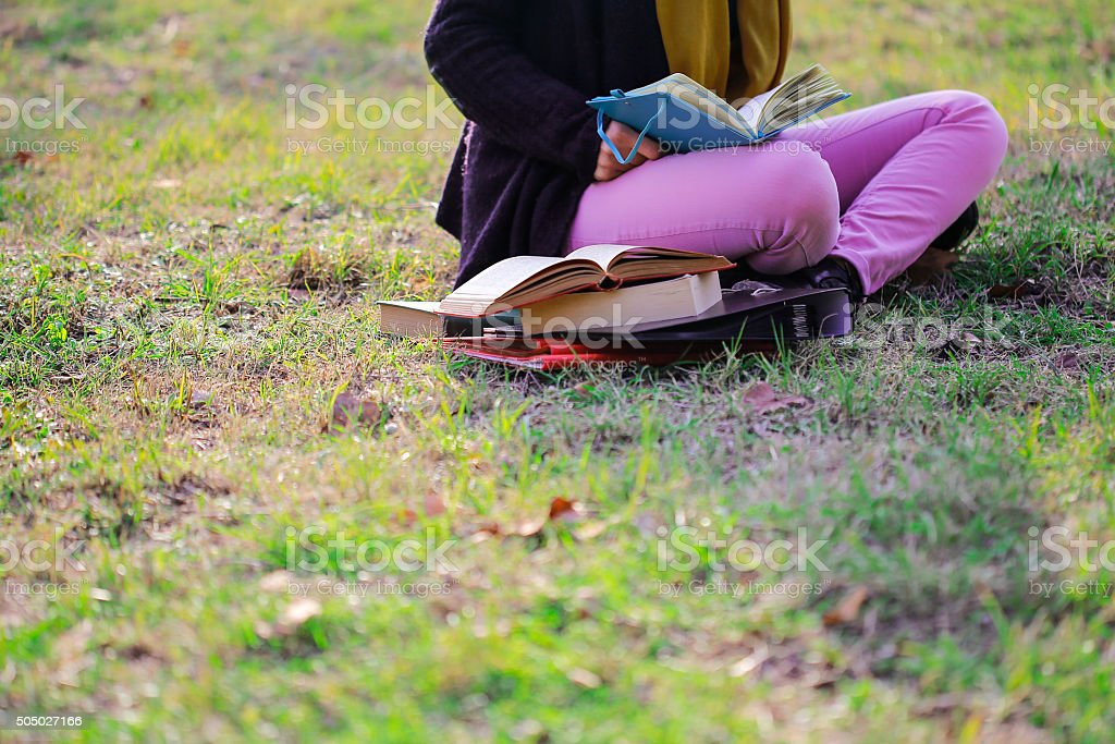 College student reading book on grass stock photo