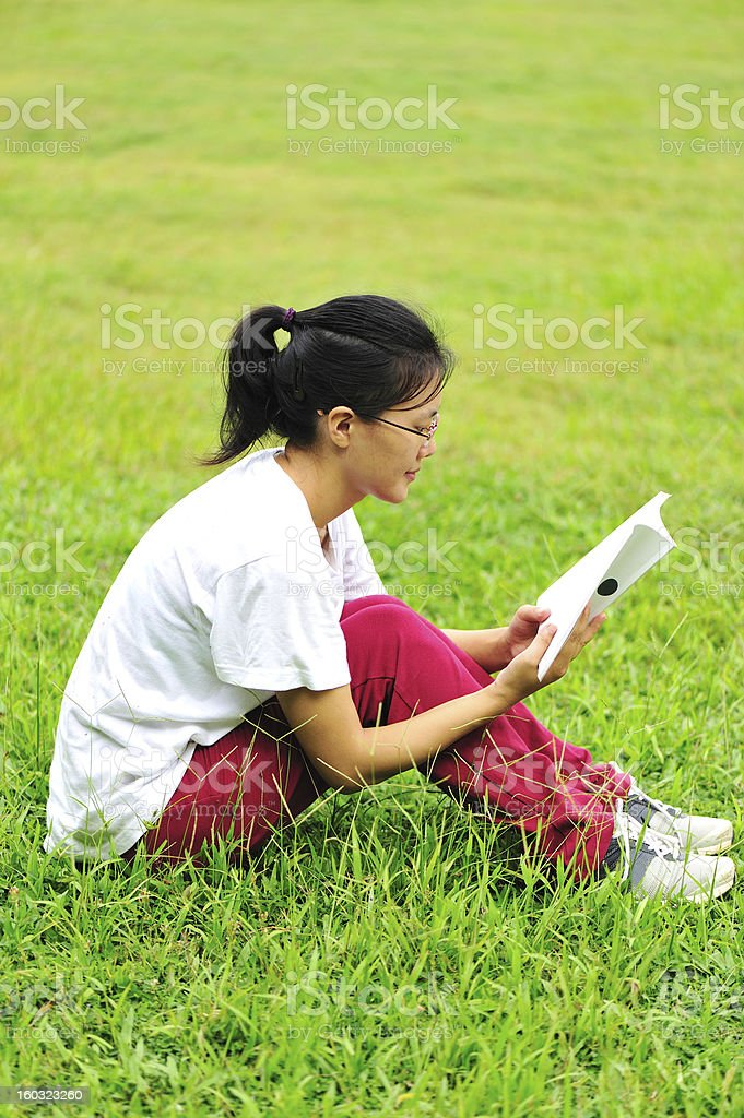 college student reading book on park grass royalty-free stock photo