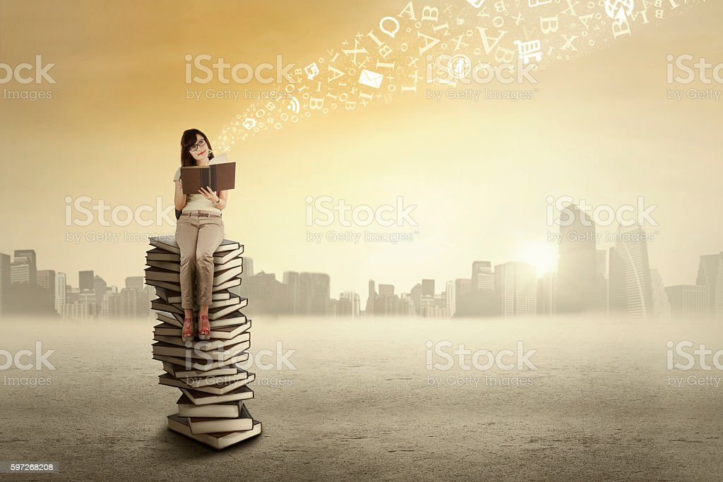 College student sits on the stack of books royalty-free stock photo