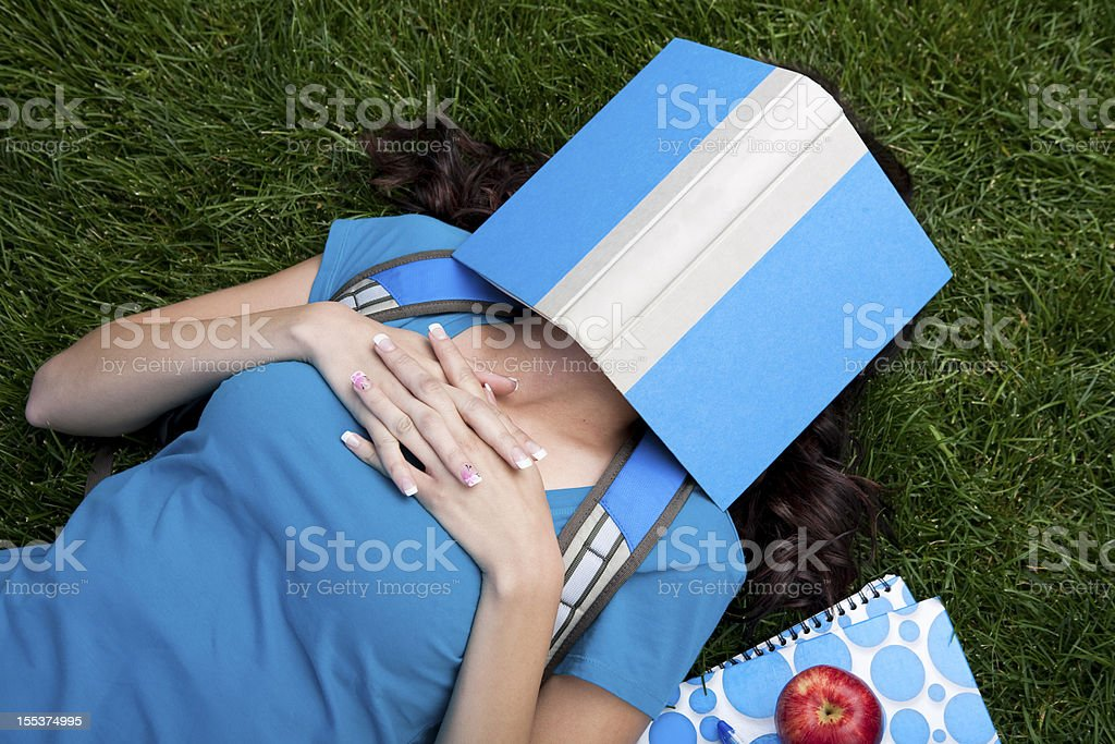 College student sleeping under her book royalty-free stock photo