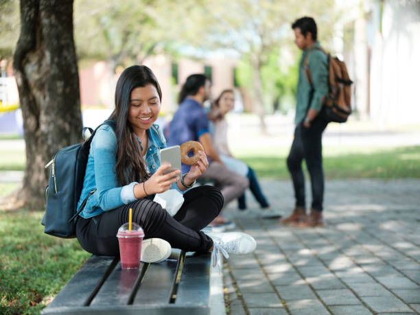 College student snacking and texting stock photo
