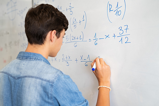Back view of high school student solving math problem on whiteboard in classroom. Young man writing math solution on white board using marker. College guy solving math expression during lesson.