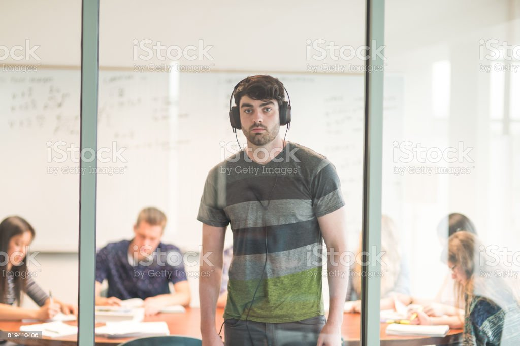 College student studies for an exam in conference room with his headphones on stock photo