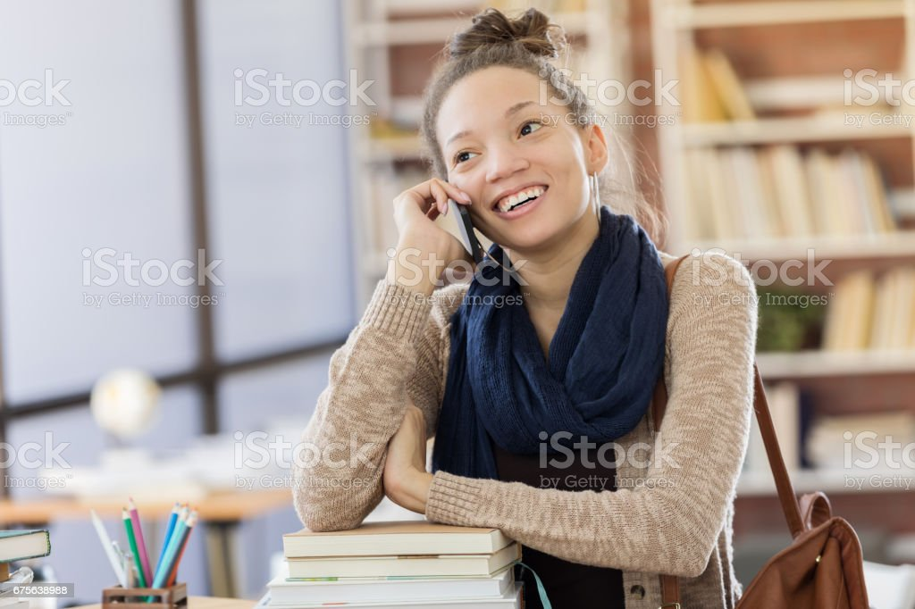 College student talks on smart phone in the library royalty-free stock photo