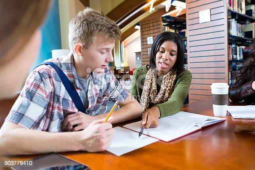 Teen or young adult African American college girl is tutoring a teenage Caucasian high school boy while they sit at table in modern school or public library. Tutor is explaining class assignment while student looks at paper. They are wearing trendy casual cothing.