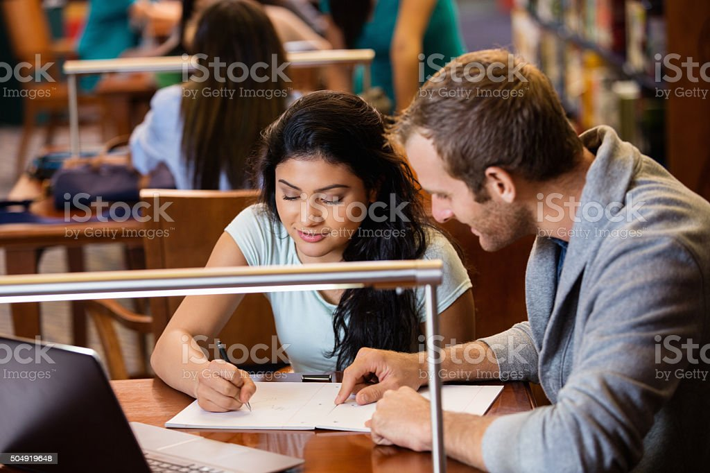 College student tutoring teenage girl in crowded public library stock photo