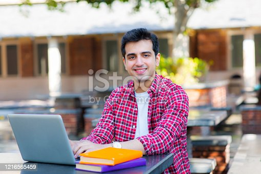 544356862 istock photo College student using a laptop in a coffee shop stock photo 1216565459