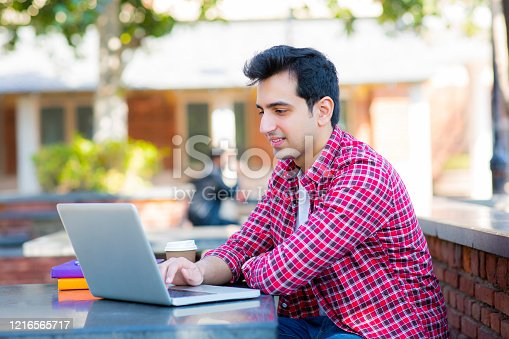 544356862 istock photo College student using a laptop in a coffee shop stock photo 1216565717