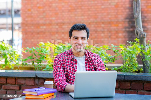 544356862 istock photo College student using a laptop in a coffee shop stock photo 1216565812