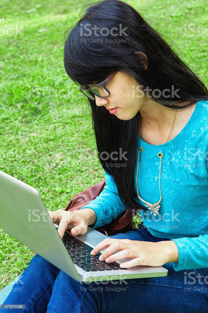College Student using computer in university park outdoor stock photo
