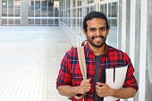 College student with backpack and books posing on campus - Stock image with copy space.
