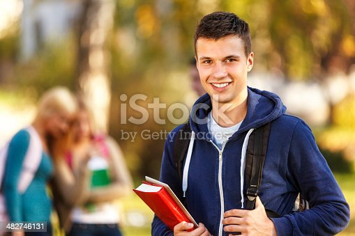 istock College student with book and digital tablet outdoor 482746131