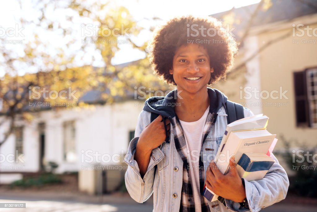 College student with lots of books in college campus stock photo