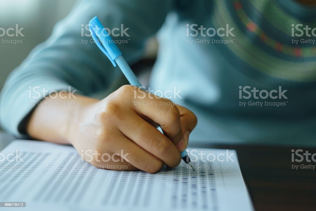 Close up of high school or university student holding a pen writing...