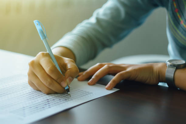 College student write on exam paper stock photo
