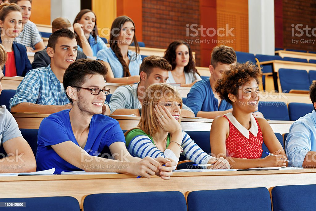 College students at the lecture College students sitting in the lecture hall at the university and listening to the lecture. 20-24 Years Stock Photo